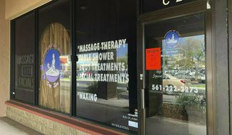 FILE- In this Feb. 19, 2019 file photo, a sign is posted outside Orchids of Asia Day Spa in Jupiter, Fla. An Associated Press review of state records shows that officers and deputies in Florida have investigated hundreds of massage parlors for illegal sexual activity for years, but the owners and employees usually get off with civil fines and misdemeanor charges, even when there are signs of potential trafficking.(Hannah Morse/Palm Beach Post via AP, File)