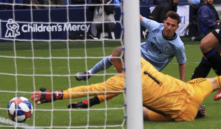 Montreal Impact goalkeeper Evan Bush reaches for the ball as Sporting Kansas City forward Krisztian Nemeth watches his shot go in the goal in the 43th minute Saturday, March 30, 2019, during an MLS match in Kansas City, Mo. (Ryan Weaver/The Kansas City Star via AP)