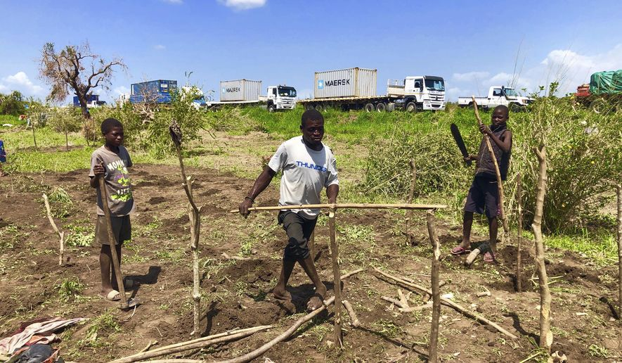 A family builds a temporary structure after their house was destroyed, on the outskirts of Beira in Mozambique, Thursday, March 28, 2019. The first cases of cholera have been confirmed in the cyclone-ravaged city of Beira, Mozambican authorities announced on Wednesday, raising the stakes in an already desperate fight to help hundreds of thousands of people sheltering in increasingly squalid conditions. (AP Photo/Tsvangirayi Mukwazhi)