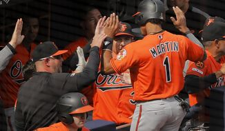 Baltimore Orioles' Richie Martin (1) is congratulated by teammates after scoring on a throwing error by New York Yankees catcher Gary Sanchez during the sixth inning of a baseball game, Saturday, March 30, 2019, in New York. (AP Photo/Julie Jacobson)