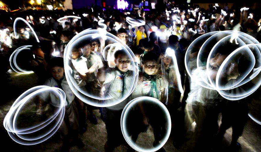 Philippine Boy Scouts play with their flashlights at the countdown for the 12th Earth Hour event Saturday, March 30, 2019 in suburban Makati city east of Manila, Philippines. Earth Hour is the symbolic switching off of the lights for one hour to help minimize fossil fuel consumption as well as mitigate the effects of climate change. (AP Photo/Bullit Marquez)