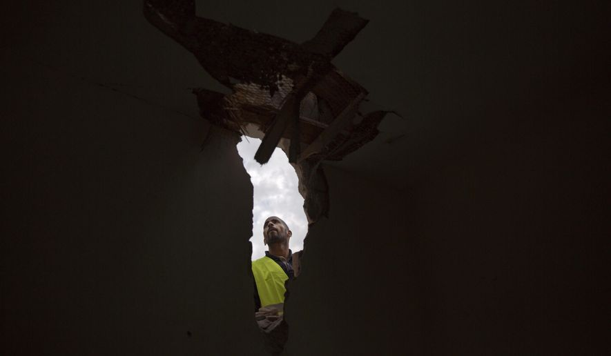 A man examines damage to a house after it was hit by a rocket on Monday in Sderot, southern Israel, Tuesday, March 26, 2019. Israel and Gaza's Hamas militants traded fire overnight after a rocket attack from Gaza struck a home in central Israel Monday. (AP Photo/Ariel Schalit)