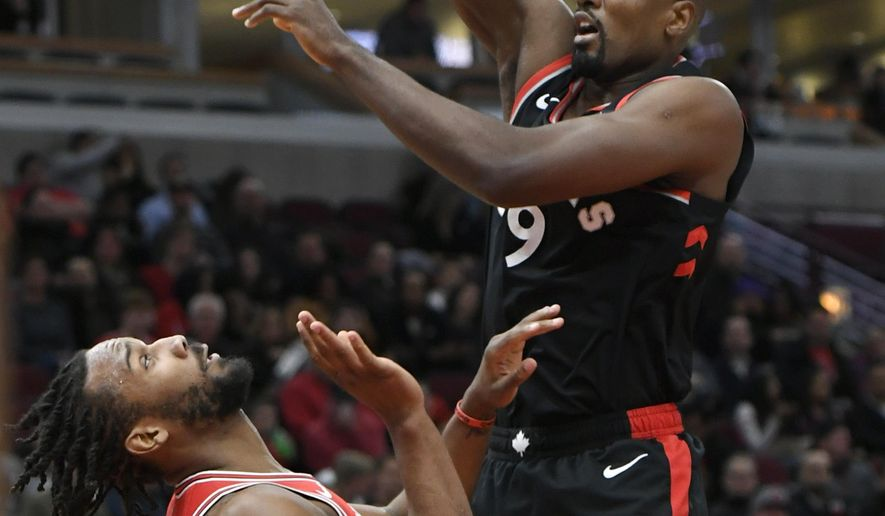 Toronto Raptors' Serge Ibaka, right, of Spain, goes up for a shot against Chicago Bulls' Wayne Selden Jr., left, during the first half of an NBA basketball game, Saturday, March 30, 2019, in Chicago. (AP Photo/Paul Beaty)