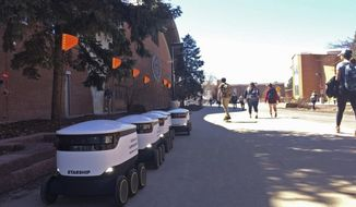 In this photo taken March 25, 2019, a row of food delivery robots awaits pickup orders outside the student union at Northern Arizona University in Flagstaff, Arizona. Dozens of cooler-size robots on wheels have begun rolling around the university's main campus in Flagstaff to deliver meals from Einstein Bros. Bagels, Cobrizo Mexican Grill and other retailers to hundreds of students a day. (Svea Conrad/Arizona Daily Sun via AP)