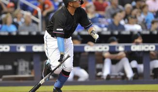 Miami Marlins' Miguel Rojas watches his RBI double during the fourth inning of the team's baseball game against the Colorado Rockies in Miami on Saturday, March 30, 2019. (AP Photo/Gaston De Cardenas)