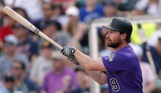 Colorado Rockies second baseman Daniel Murphy (9) follows through on a two-run home run in the first inning of a spring training baseball game against the Minnesota Twins Tuesday, March 26, 2019, in Fort Myers, Fla. (AP Photo/John Bazemore)