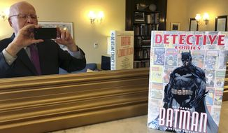 This Thursday, March 28, 2019, photo provided by Sen. Patrick Leahy, D-Vt., shows Leahy in a mirror and the 80th anniversary edition of a book commemorating the superhero Batman. Leahy, who wrote the forward for the book, has been a Batman fan since first reading the comic books as a child growing up in the 1940s in Montpelier, Vt. Leahy also has made brief appearances in a number of Batman movies. (Sen. Patrick Leahy via AP)
