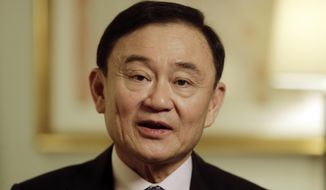 FILE - In this March 9, 2016, file photo, Thailand's former Prime Minister Thaksin Shinawatra responds to questions during a interview in New York. Thailand's king has stripped fugitive former Prime Minister Thaksin of his royal decorations, citing his 2008 flight to escape serving a two-year prison term on a conflict of interest conviction and other legal cases against him. Thai media reported that the Royal Command from King Maha Vajiralongkorn was published Saturday, March 30, 2019 in the Royal Gazette. (AP Photo/Frank Franklin II, File)