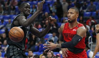 Portland Trail Blazers guard Damian Lillard, right, passes as Detroit Pistons forward Thon Maker, left, defends during the first half of an NBA basketball game, Saturday, March 30, 2019, in Detroit. (AP Photo/Carlos Osorio)