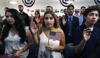 Ericka Ames, center, 18, of Nicaragua recites the Oath of Allegiance during a naturalization ceremony at the U.S. Citizenship and Immigration Services Kendall Field Office, Thursday, Aug. 30, 2018, in Miami. (AP Photo/Wilfredo Lee) ** FILE **