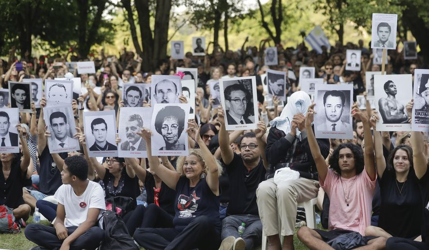 Demonstrators hold photos of persons who were killed during Brazil's dictatorship during a protest in Sao Paulo, Brazil, Sunday, March 31, 2019. Over the objections of human rights groups but with the support of far-right President Jair Bolsonaro, some military bases are commemorating the March 31, 1964 coup that lasted two decades in Brazil and made thousands of victims. (AP Photo/Andre Penner)