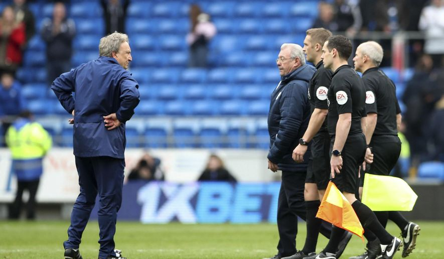 Cardiff City manager Neil Warnock, left, stands on the pitch after Chelsea won the match 2-1, during the English Premier League soccer match at the Cardiff City Stadium in Cardiff, Wales, Sunday March 31, 2019. (Nick Potts/PA via AP)