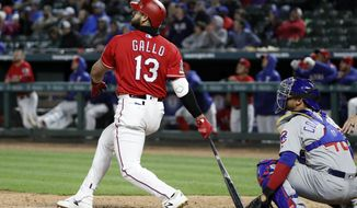 Texas Rangers' Joey Gallo (13) and Chicago Cubs catcher Willson Contreras (40) watch Gallo's three-run home run during the eighth inning of a baseball game in Arlington, Texas, Saturday, March 30, 2019. (AP Photo/Tony Gutierrez)