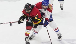 FILE - In this Sunday, March 24, 2019, file photo, Calgary Inferno's Brigette Lacquette, left, battles for the puck with Les Canadiennes de Montreal's Lauriane Rougeau during the second-period action of the Clarkson Cup hockey game in Toronto, Ontario. The Canadian Women's Hockey League will discontinue operations on May 1, the league announced Sunday, March 31. (Chris Young/The Canadian Press via AP, File)