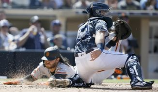 San Francisco Giants' Brandon Crawford, left, slides into home to beat the throw to San Diego Padres catcher Austin Hedges, right, on an RBI double by Pablo Sandoval during the fifth inning of a baseball game in San Diego, Sunday, March 31, 2019. (AP Photo/Alex Gallardo)