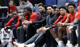 New Orleans Pelicans forward Anthony Davis, center, watches from the bench in street clothes in the first half of an NBA basketball game against the Atlanta Hawks in New Orleans, Tuesday, March 26, 2019. (AP Photo/Gerald Herbert)
