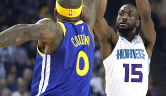 Charlotte Hornets guard Kemba Walker (15) takes a 3-point shot over Golden State Warriors center DeMarcus Cousins (0) during the first half of an NBA basketball game Sunday, March 31, 2019, in Oakland, Calif. (AP Photo/Tony Avelar)