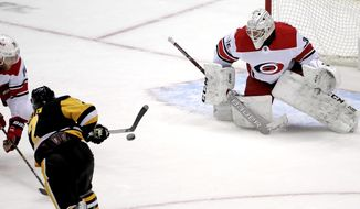 Pittsburgh Penguins' Matt Cullen (7) gets a shot past Carolina Hurricanes goaltender Curtis McElhinney (35) for a goal with Hurricanes' Jaccob Slavin (74) defending during the first period an NHL hockey game in Pittsburgh, Sunday, March 31, 2019. (AP Photo/Gene J. Puskar)