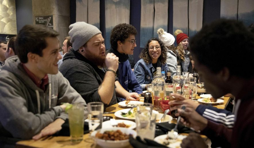 In this Nov. 9, 2018 photo, NextGen Wisconsin organizers from across the state, Joe Waldman, from left, regional organizing director, Krish Colon, for University of Wisconsin-Parkside, Maxwell Coleman, for Waukesha County, and Selma Aly, for Marquette University, have dinner together to celebrate Democrat Gov. Tony Evers' win in the 2018 gubernatorial election in Madison, Wis. Wisconsin saw about 80,000 more young voters in 2018 than 2014, helping to elect Evers. Wisconsin was one of 11 states targeted by NextGen America, a $33 million campaign to turn out young progressives. (Emily Hamer/Wisconsin Center for Investigative Journalism via AP)