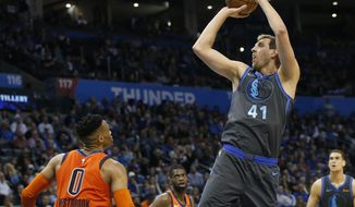 Dallas Mavericks forward Dirk Nowitzki (41) shoots over Oklahoma City Thunder guard Russell Westbrook (0) in the first half of an NBA basketball game Sunday, March 31, 2019, in Oklahoma City. (AP Photo/Sue Ogrocki)