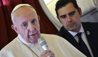 Pope Francis, flanked by interim director of Holy See Press Office, Alessandro Gisotti, speaks to reporters on board the flight back to Rome from a two-day trip to Morocco, Sunday, March 31, 2019.  Francis sought Sunday to encourage greater fraternity between Christians and Muslims in Morocco, telling his flock that showing the country's Muslim majority they are part of the same human family will help stamp out extremism. (Alberto Pizzoli/Pool Photo via AP)