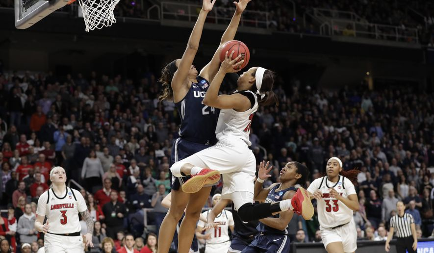 Connecticut forward Napheesa Collier (24) defends against Louisville guard Asia Durr (25) who goes up for two points during the second half of a regional championship final in the NCAA women's college basketball tournament, Sunday, March 31, 2019, in Albany, N.Y. Louisville forward Sam Fuehring (3), guard Arica Carter (11) and forward Bionca Dunham (33) watch from the floor. (AP Photo/Kathy Willens)