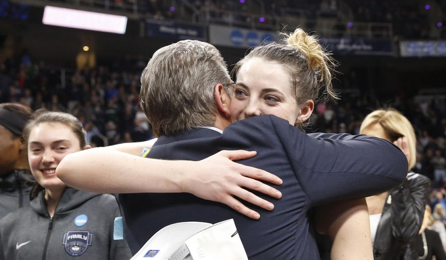 Connecticut head coach Geno Auriemma, front left, and top scorer Connecticut guard Katie Lou Samuelson embrace after defeating Louisville in a regional championship final in the NCAA women's college basketball tournament, Sunday, March 31, 2019, in Albany, N.Y. (AP Photo/Kathy Willens)