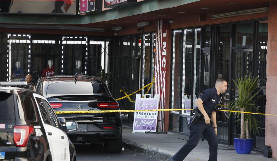 A Los Angeles Police officer walks past the taped Marathon Clothing store of Rapper Nipsey Hussle in Los Angeles, Sunday, March 31, 2019. (AP Photo/Damian Dovarganes)