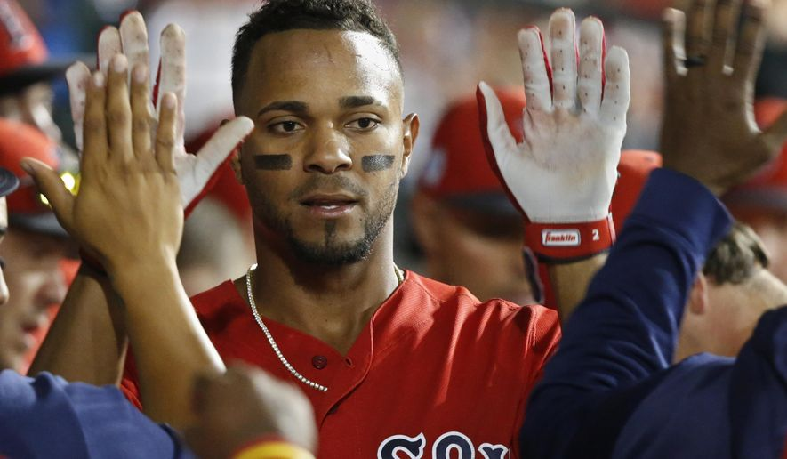 Boston Red Sox's Xander Bogaerts gets high-fives in the dugout after scoring during the seventh inning of the team's spring training baseball game against the Chicago Cubs on Monday, March 25, 2019, in Mesa, Ariz. (AP Photo/Sue Ogrocki)