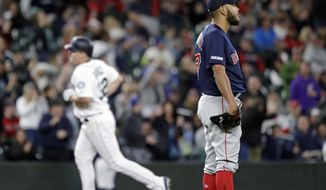 Boston Red Sox starting pitcher Eduardo Rodriguez, right, looks away as Seattle Mariners' Jay Bruce rounds the bases behind on his three-run home run in the fifth inning of a baseball game Saturday, March 30, 2019, in Seattle. (AP Photo/Elaine Thompson)