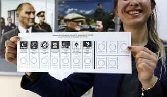 An official female shows the ballot voting paper with names and the parties a polling station during the municipal elections in Ankara, Turkey, Sunday, March 31, 2019. Turkish citizens have begun casting votes in municipal elections for mayors, local assembly representatives and neighborhood or village administrators that are seen as a barometer of Erdogan's popularity amid a sharp economic downturn. (AP Photo/Burhan Ozbilici)