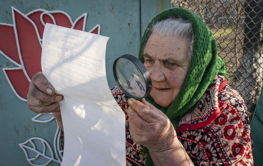 An elderly woman examines her ballot voting at home during the presidential election in Mariinka, near a contact line not far from Donetsk, eastern Ukraine, Sunday, March 31, 2019. Ukrainians choose from among 39 candidates for a president they hope can guide the country of more than 42 million out of troubles including endemic corruption, a seemingly intractable conflict with Russia-backed separatists in the country's east and a struggling economy. (AP Photo/Evgeniy Maloletka)