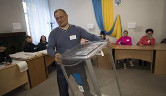 An electoral worker holds a ballot box at a polling station, during the presidential elections in Kiev, Ukraine, Sunday, March. 31, 2019. (AP Photo/Emilio Morenatti)