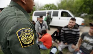 In this Thursday, March 14, 2019, photo, a Border Patrol agent talks with a group suspected of having entered the U.S. illegally near McAllen, Texas. While many adults crossing the border on their own in South Texas try to flee agents, most migrant parents and children wait to surrender so they can be processed and released into the United States. (AP Photo/Eric Gay)