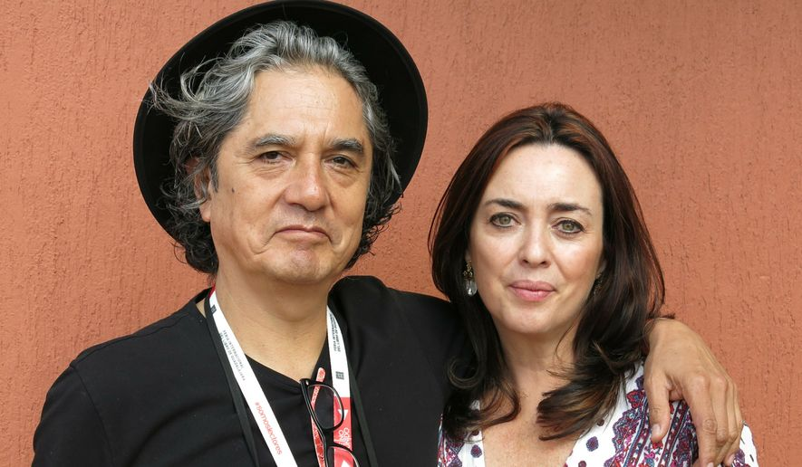 In this Dec. 5, 2015, file photo, Mexican musician Armando Vega Gil, left, and author Beatriz Rivas pose for a portrait during the Guadalajara International Book Fair in Guadalajara, Mexico. The Mexican rock band Botellita de Jerez announced on Monday, April 1, 2019, the death of its founder Armando Vega Gil. The musician and writer had posted a message announcing his suicide. (AP Photo/Berenice Bautista, File)
