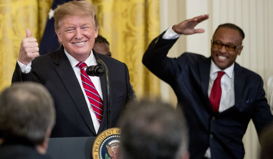 Gregory Allen, a First Step Act beneficiary, right, salutes after being invited to the podium to speak by President Donald Trump, left, during the 2019 Prison Reform Summit and First Step Act Celebration in the East Room of the White House in Washington, Monday, April 1, 2019. (AP Photo/Andrew Harnik)