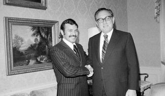 FILE - In this Oct. 1, 1975 file photo Abdelaziz Bouteflika, left, meets with U.S. Secretary of State Henry Kissinger at the U.S. State Department suite at the Waldorf Astoria Hotel Towers. Algerian President Abdelaziz Bouteflika's office announced Monday that he will step down by the end of his current term April 28, ceding to weeks of mass protests against his rule. It was a stunning concession for the 82-year-old leader, who has been diminished by a stroke but has been known as a wily political survivor ever since he fought for independence from France six decades ago. (AP Photo/Dave Pickoff, File)