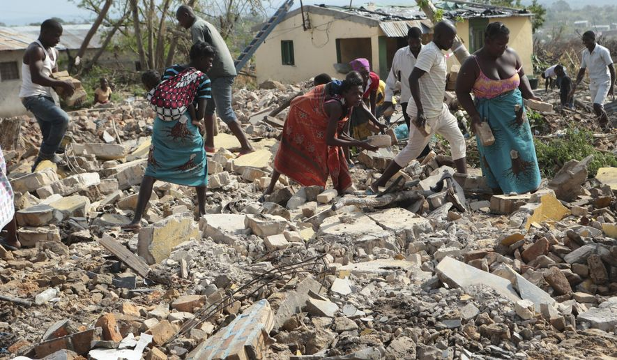 Women and men pick up bricks from a collapsed house to build another structure in Beira, Mozambique, Sunday, March, 31, 2019. Cholera cases among cyclone survivors in Mozambique have jumped to 271, authorities said. So far no cholera deaths have been confirmed, the report said. Another Lusa report said the death toll in central Mozambique from the cyclone that hit on March 14 had inched up to 501. Authorities have warned the toll is highly preliminary as flood waters recede and reveal more bodies. (AP Photo/Tsvangirayi Mukwazhi)