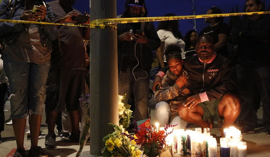 Haitian-French actor Jimmy Jean-Louis and his daughter Jasmin, 16, gather around candles set up across from the clothing store of rapper Nipsey Hussle in Los Angeles, Sunday, March 31, 2019. Hussle, the skilled and respected West Coast rapper who had a decade-long success with mixtapes but hit new heights with his Grammy-nominated major-label debut album in 2018, has died. He was 33. (AP Photo/Damian Dovarganes)