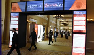 FILE - This April 26, 2018, file photo shows CinemaCon attendees walking through the lobby during CinemaCon 2018 in Las Vegas, the official convention of the National Association of Theatre Owners. The movie industry, everyone from the Hollywood studios that produce the films to the companies that make the screens, speakers and seats in theaters, are descending on Las Vegas this week for CinemaCon. (Photo by Chris Pizzello/Invision/AP, File)
