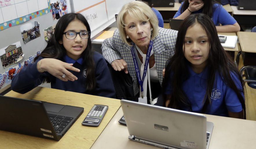 U.S. Education Secretary Betsy DeVos talks with students in a sixth grade math class at Cameron Middle School Monday, April 1, 2019, in Nashville, Tenn. DeVos said she's encouraged by Tennessee's latest push to expand school vouchers throughout the state and said she's cheering on lawmakers to make the right choice. (AP Photo/Mark Humphrey)