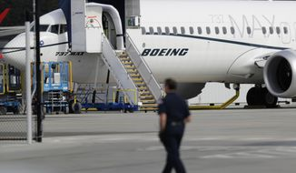 FILE - In this March 14, 2019, file photo, a worker walks next to a Boeing 737 MAX 8 airplane parked at Boeing Field in Seattle. U.S. aviation regulators said Monday, April 1, Boeing needs more time to finish changes in a flight-control system suspected of playing a role in two deadly crashes. (AP Photo/Ted S. Warren, File)