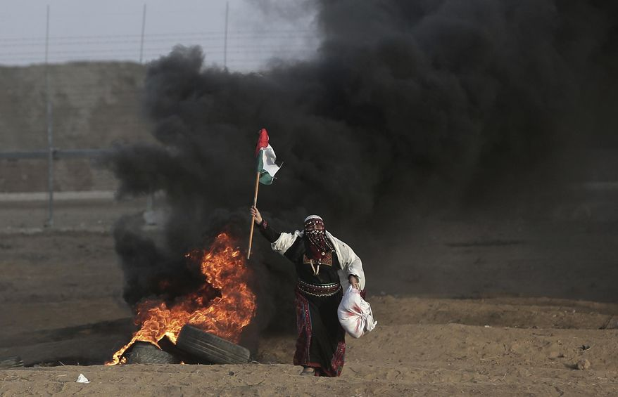 FILE - In this Oct. 5, 2018 file photo, a Palestinian woman carries a Palestinian flag during a protest at the Gaza Strip's border with Israel. Hamas controls Gaza more tightly than ever, despite unprecedented domestic unrest and its failure to significantly weaken Israel's chokehold of the territory after a year of weekly anti-blockade rallies along their shared frontier. (AP Photo/Khalil Hamra, File)