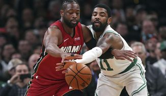Boston Celtics guard Kyrie Irving (11) reaches in on a steal-attempt against Miami Heat guard Dwyane Wade (3) during the first quarter of an NBA basketball game in Boston, Monday, April 1, 2019. (AP Photo/Charles Krupa)