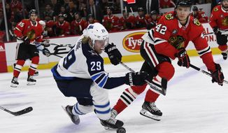 Winnipeg Jets right wing Patrik Laine (29) and Chicago Blackhawks defenseman Gustav Forsling (42) fight for the puck during the first period of an NHL hockey game Monday, April 1, 2019, in Chicago. (AP Photo/Matt Marton)