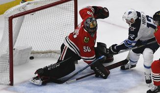 Winnipeg Jets right wing Kevin Hayes (12) scores the winning goal in overtime past Chicago Blackhawks goaltender Corey Crawford (50) during an NHL hockey game Monday, April 1, 2019, in Chicago. (AP Photo/Matt Marton)