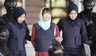 Vietnamese Doan Thi Huong, center, is escorted by police as she leaves Shah Alam High Court in Shah Alam, Malaysia, Monday, April 1, 2019. The Vietnamese woman who is the only suspect in custody for the killing of the North Korean leader's brother Kim Jong Nam pleaded guilty to a lesser charge in a Malaysian court on Monday and her lawyer said she could be freed as early as next month. (AP Photo/Vincent Thian)