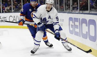Toronto Maple Leafs' John Tavares (91) looks to pass away from New York Islanders' Johnny Boychuk (55) during the first period of an NHL hockey game Monday, April 1, 2019, in Uniondale, N.Y. (AP Photo/Frank Franklin II)