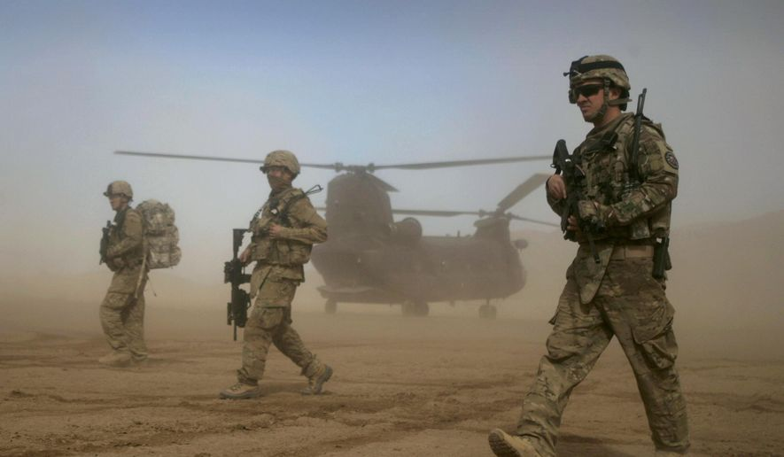 In this Saturday, Jan. 28, 2012, file photo, U.S. soldiers, part of the NATO-led International Security Assistance Force (ISAF) walk west of Kabul, Afghanistan. (AP Photo/Hoshang Hashimi, File)