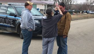 "Gina Kessel, center, comforts her son Mitchell outside of RJR Maintenance and Management, a property management company, Monday, April 1, 2019, Mandan, N.D. Authorities say police responding to a medical call at the North Dakota business have found ""several"" bodies. The Mandan Police Department issued a three-sentence news release confirming that officers had found ""several people who were deceased inside"" the business in the city of about 22,000 just across the Missouri River west of Bismarck. (AP Photo/Blake Nicholson)"